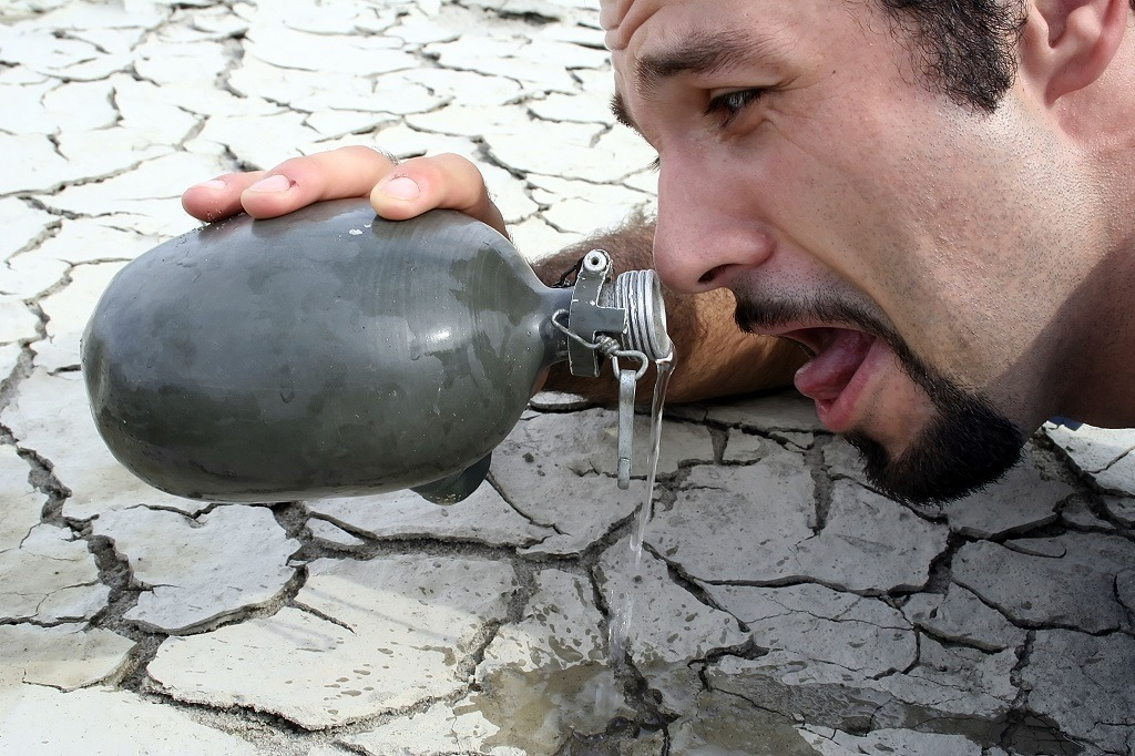 man with cottonmouth trying to drink water